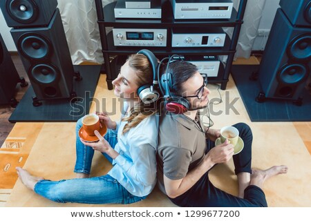 Photo stock: Couple With Headphones Enjoying Music From The Hi Fi Stereo