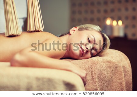 woman having samurai massage with bamboo brooms Stock photo © dolgachov