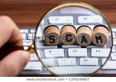 Hand Holding Magnifying Glass Over Wooden Cork On Keyboard Stock photo © AndreyPopov