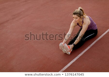 Young woman doing some exercises and streching legs at the court Stock photo © boggy