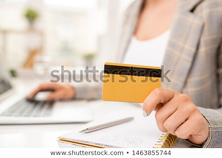 Yellow credit card with black magnet line held by contemporary businesswoman Stock photo © pressmaster