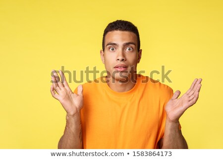 Shook and clueless handsome young man, spread hands sideways, shrugging indecisive, cant tell, dont  Stock photo © benzoix