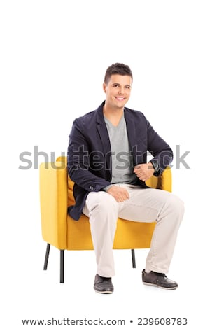 Handsome young man sitting and posing in armchair in modern luxury interior Stock photo © GVS