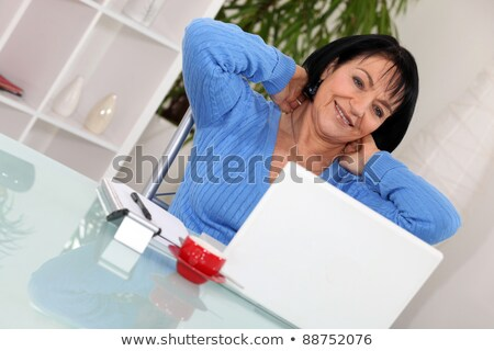 a middle age woman stretching in front of her computer stock photo © photography33