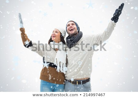 Attractive young couple in warm clothes with arms up Stock photo © wavebreak_media