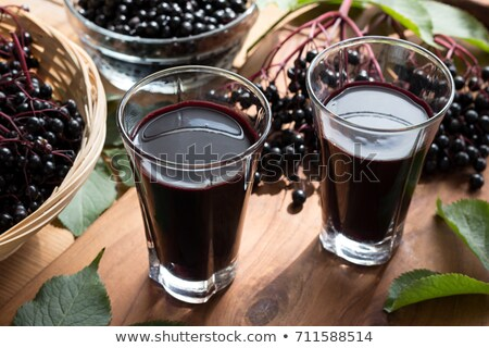 Two glasses of black elder syrup with fresh elderberries Stock photo © madeleine_steinbach