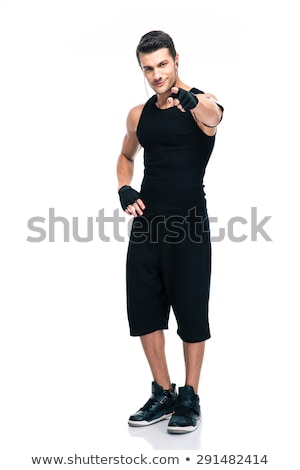 Souriant homme pointant biceps bel homme posant Photo stock © NeonShot
