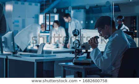 Scientist in a laboratory works with an electron microscope gateway. Putting a sample into a chamber Stock photo © galitskaya