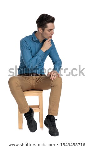 pensive smart casual man sitting and looking down to side stock photo © feedough