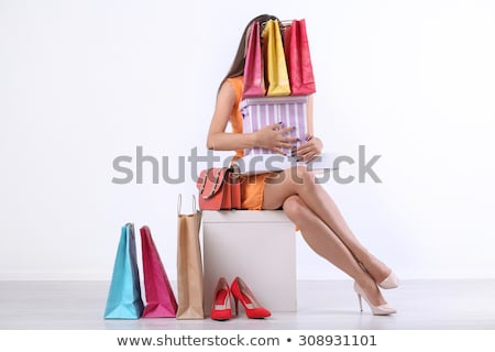 Beautiful young woman with shopping bags and boxes isolated on pink. Stock photo © studiolucky