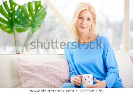 beautiful blond woman drinking a coffee while sitting on her bed at home stock photo © dash