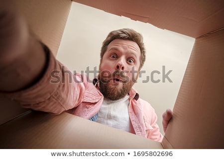 shocked man looking into open parcel box Stock photo © dolgachov