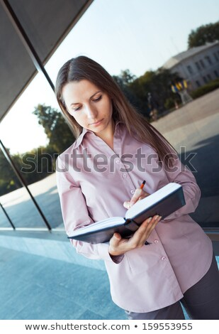 Businesswoman make notes in organizer while standing against off Stock photo © vlad_star