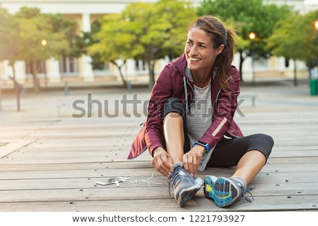 happy sporty woman tying shoelaces stock photo © deandrobot