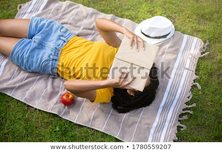 African young woman lies outdoors in park reading book. Stock photo © deandrobot
