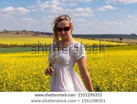 Female  by a field of flowering canola and rolling hills Stock photo © lovleah