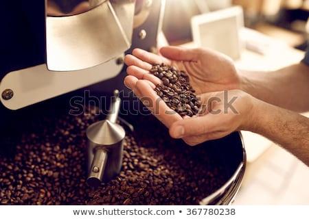Man with freshly roasted coffee beans Stock photo © Kzenon