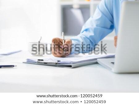 businessman - writing on clipboard stock photo © dgilder