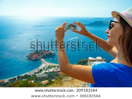 Girl  making photos by the smartphone island of Sveti Stefan, Mo Stock photo © vlad_star
