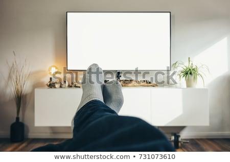Człowiek pilota oglądania telewizja domu ludzi Zdjęcia stock © dolgachov