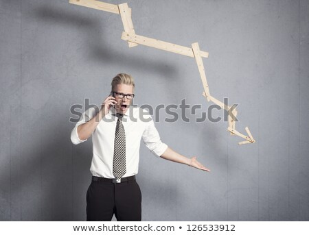 Angry businessman in front of graph pointing down. Stock photo © lichtmeister