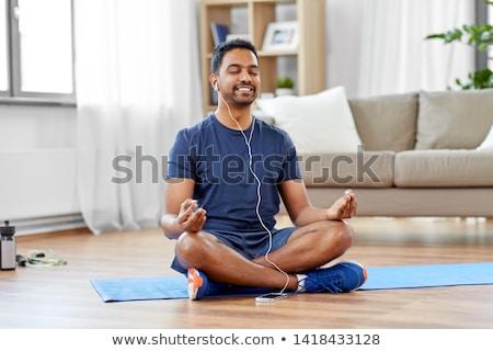 indian man meditating in lotus pose at home Stock photo © dolgachov