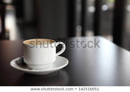 Milk and a cup of coffee on white plates with sugar and spoon against a white background Stock photo © wavebreak_media