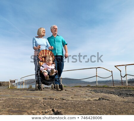 mature couple pushing child in buggy Stock photo © IS2