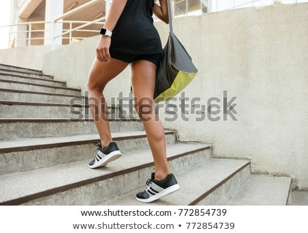 Close up of a woman dressed in sportswear carrying bag Stock photo © deandrobot
