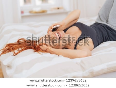 Vivacious woman relaxing in bed laughing as she listens to a call on her mobile phone with her red h Stock photo © ElenaBatkova