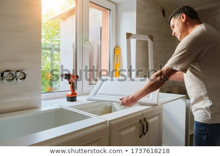 Carpenter Assembling Cabinet On Wall In Kitchen Stock photo © AndreyPopov