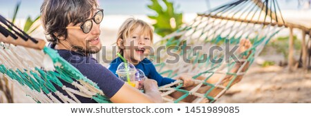 Young man on the beach in a hammock with a drink BANNER, LONG FORMAT Stock photo © galitskaya