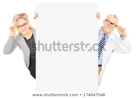 Aged woman standing behind blank billboard stock photo © stockyimages