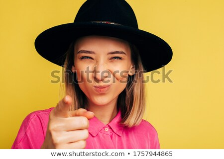 fashionable brunette pointing forward with closed eyes stock photo © stockyimages