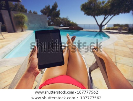Tanned young woman using a tablet computer Stock photo © dash