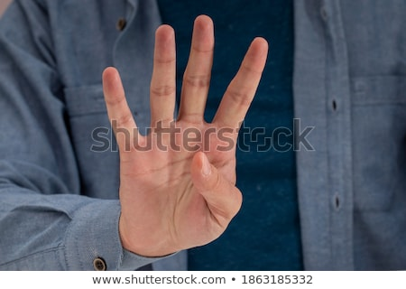 Closeup of arm - hand making number four sign. stock photo © dgilder