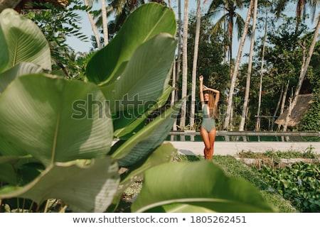 Beautiful woman in green bikini relaxing by poolside Stock photo © wavebreak_media