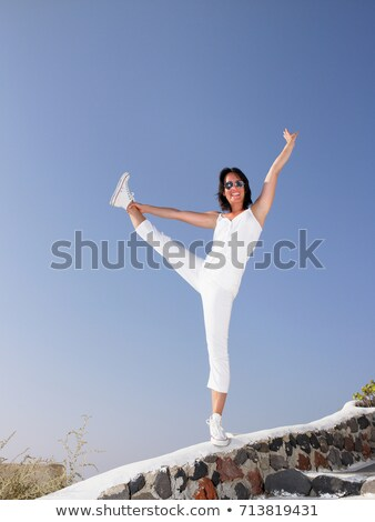 Woman holding her leg, on a low wall Stock photo © IS2