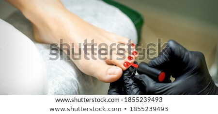 pedicurist applying white color to foot nails of woman stock photo © kzenon