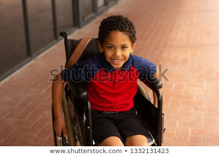 Stock photo: High angle view of happy smiling mixed-race disabled schoolboy looking at camera in corridor at elem