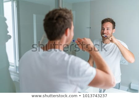 Man getting ready in the morning doing hygiene routine brushing his teeth looking in mirror of home  Stock photo © Maridav