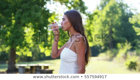 Brunette drinking glass of water outdoors Stock photo © photography33