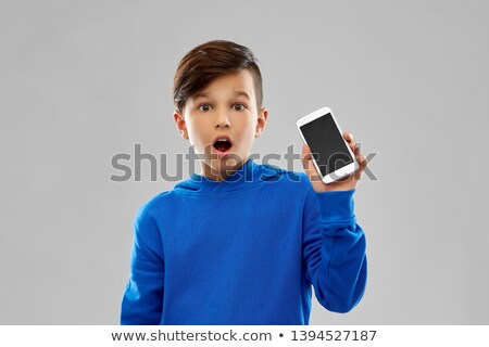 shocked boy in blue hoodie showing smartphone Stock photo © dolgachov
