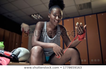 Female boxer is wrapping hands with boxing wraps Stock photo © GVS