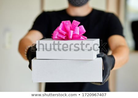 Courier man contactless delivery presents, gift box during a coronavirus epidemic. Stock photo © Illia