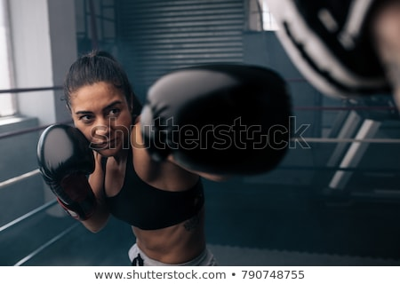 Female boxer practicing in the boxing ring Stock photo © dashapetrenko