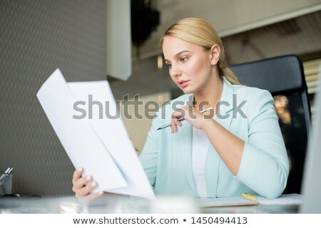 young serious teacher with pencil checking papers of students stock photo © pressmaster