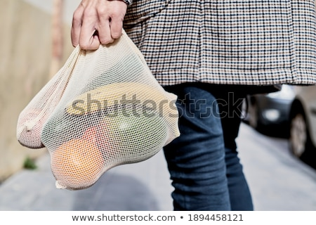 man carrying mesh bags full of fruit and vegs