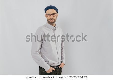 Sideways shot of handsome pleased man wears stylish hat, keeps hands in pockets, stands against whit Stock photo © vkstudio