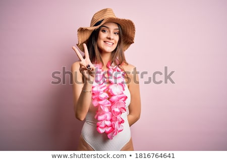 woman showing a pink flower while smiling stock photo © wavebreak_media